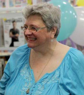A woman laughing. There are party balloons in the background.
